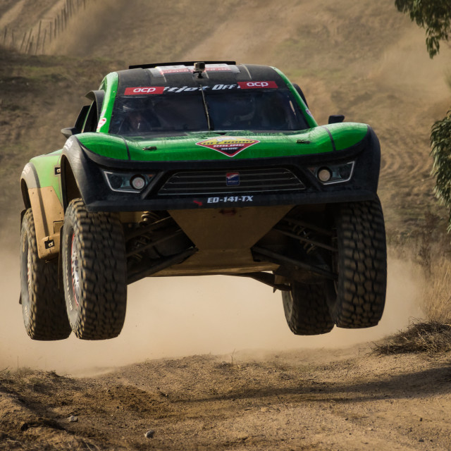 """A Mitjet OffRoad off-road race car makes a jump on a dirt road"" stock image"