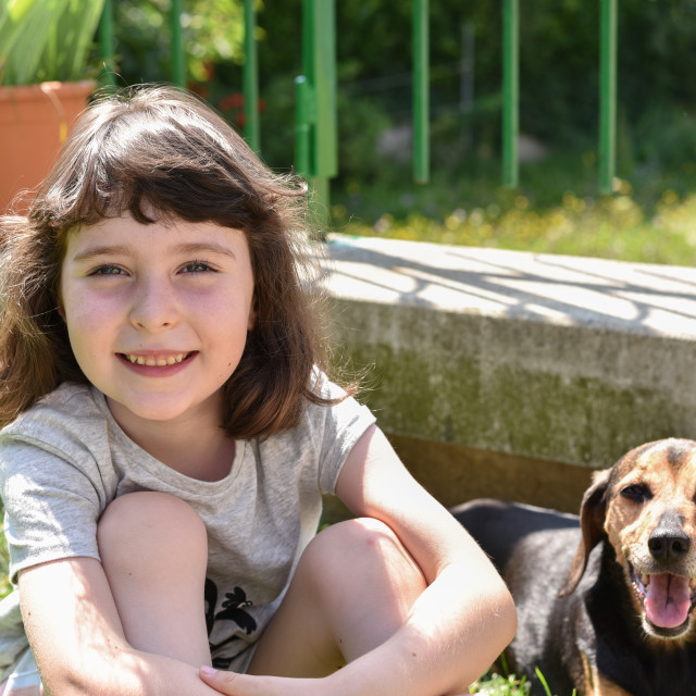 """""""Little girl sits outdoors next to her dog"""" stock image"""