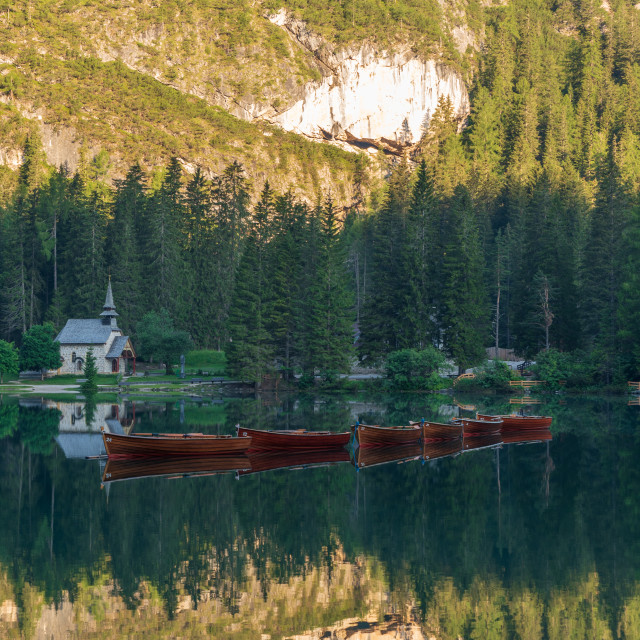 """""""Row of wooden boats in front of a church reflected in the water"""" stock image"""