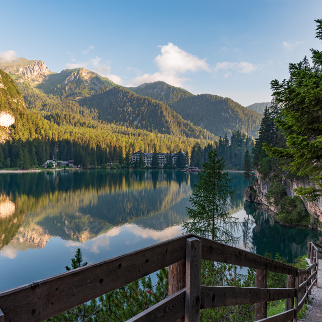 """""""A path with a wooden fence climbs steeply beside the Braies lake"""" stock image"""