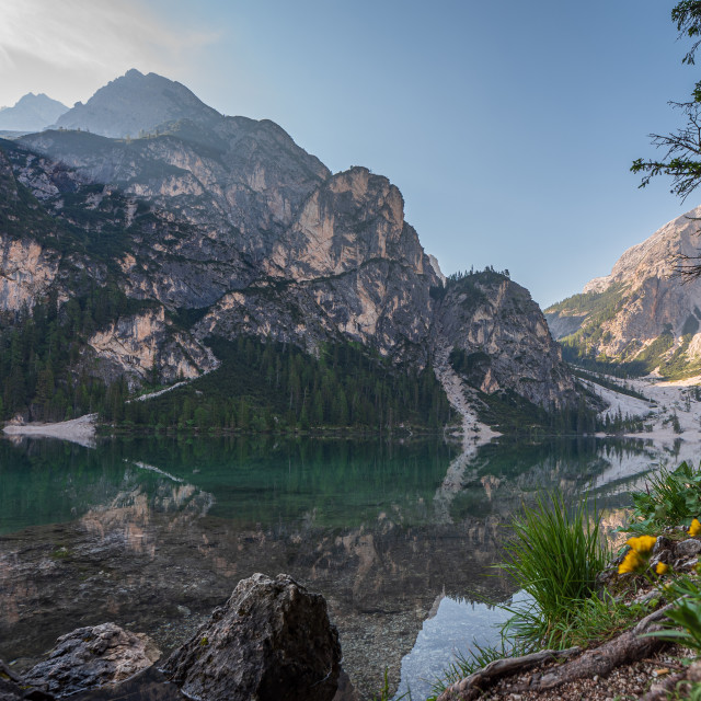 """""""Braies Lake and its reflections seen from a beach between rocks"""" stock image"""
