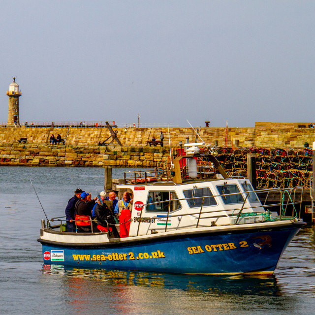 """""""Sea Otter 2 Returning to Whitby Harbour on Yorkshires East Coast after a Fishing Trip. Pier and Lighthouse in the Background."""" stock image"""