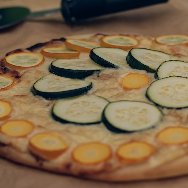 """Zucchini pizza with cutter in backgroun"" stock image"