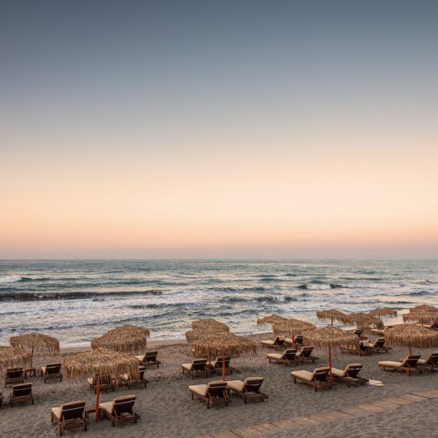 """Sun loungers with umbrella on the beach, sunrise."" stock image"