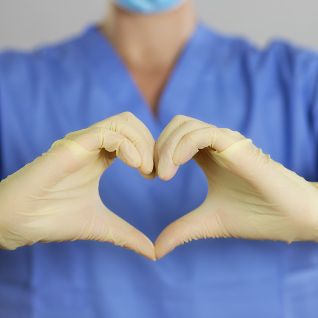 """""""Doctor or nurse in a blue shirt makes the heart symbol with hands in gloves."""" stock image"""