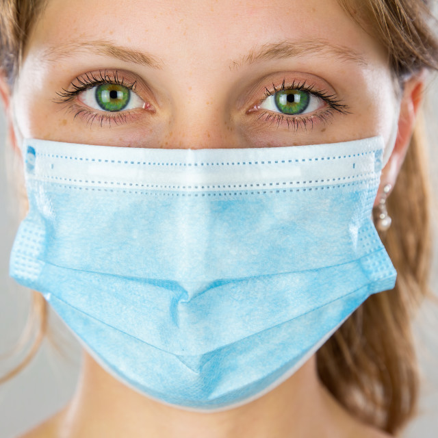 """""""Close-up of a alert young blonde woman with face mask looking into camera"""" stock image"""