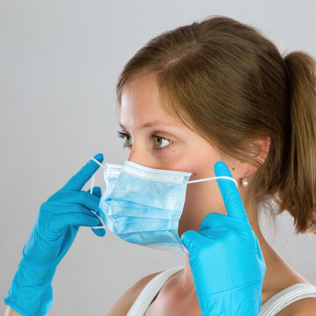 """""""Young woman with blond hair putting on face mask from side view"""" stock image"""