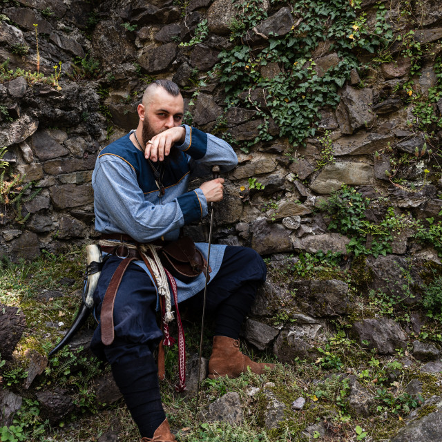 """""""A Viking sitting with his sword in front of a stone wall"""" stock image"""