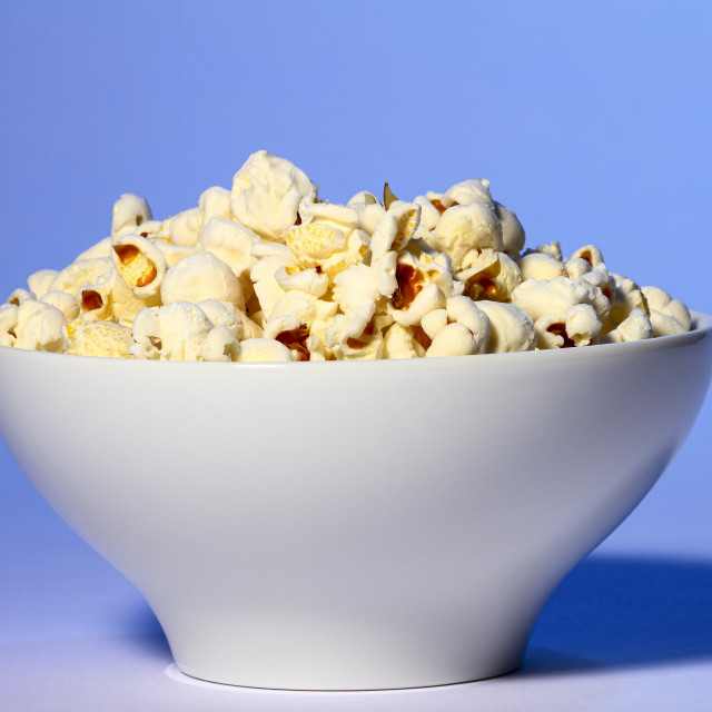 """Bowl of fresh popcorn isolated on a blue background"" stock image"