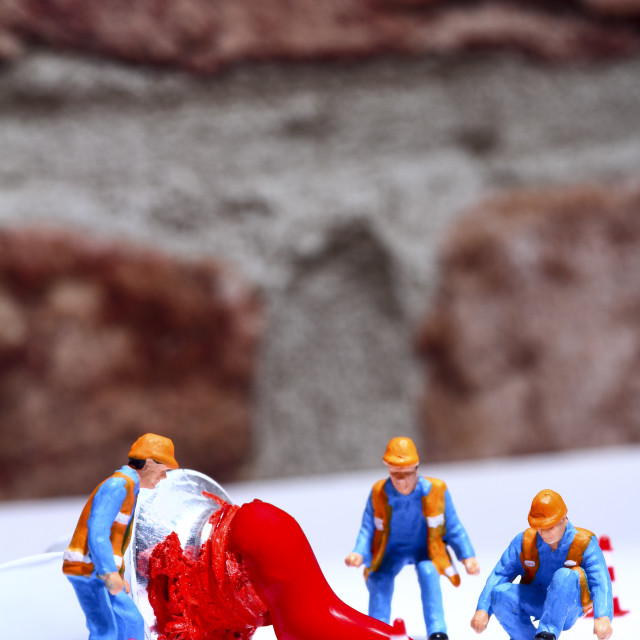 """""""Miniature figure people investigating an artists red paint tube spillage"""" stock image"""