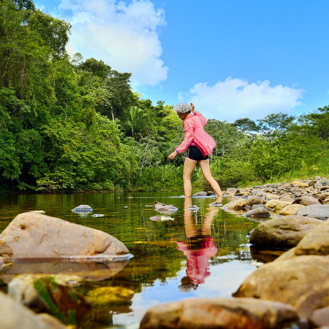 """""""Woman stepping into a river"""" stock image"""