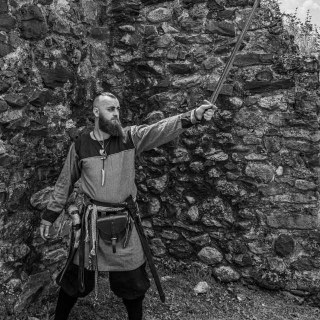 """""""Viking warrior draws his sword in front of a stone wall"""" stock image"""