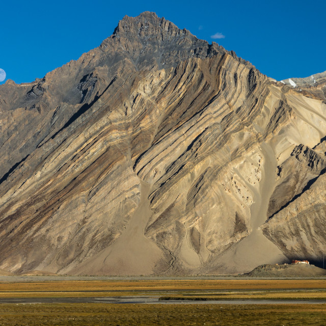 """Zanskar Mountains cliff with clearly visible sediment rock layers, Rangdum Gompa and the rising moon"" stock image"