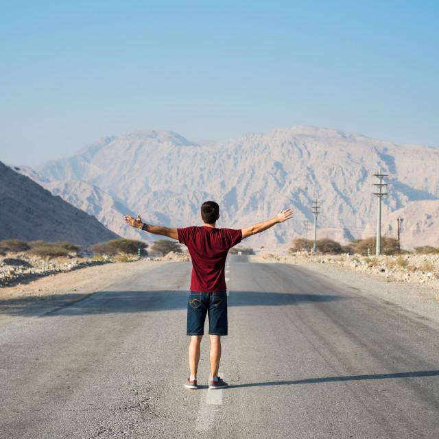 """Man standing on the empty dessert road"" stock image"