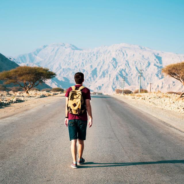 """Man walking on the empty dessert road"" stock image"