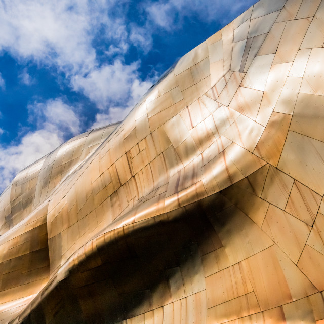 """Wavy bronze cladding against a blue sky"" stock image"