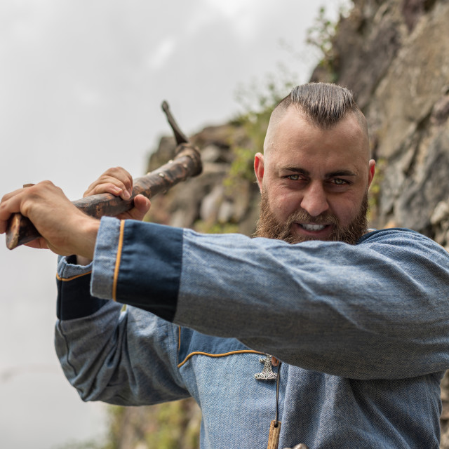 """""""A man in medieval clothes wields an ax in the ruins of an ancien"""" stock image"""