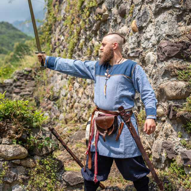 """""""Medieval warrior brandishes his sword raising it to the sky"""" stock image"""