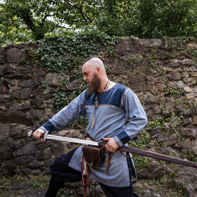 """""""Medieval warrior draws sword from scabbard"""" stock image"""