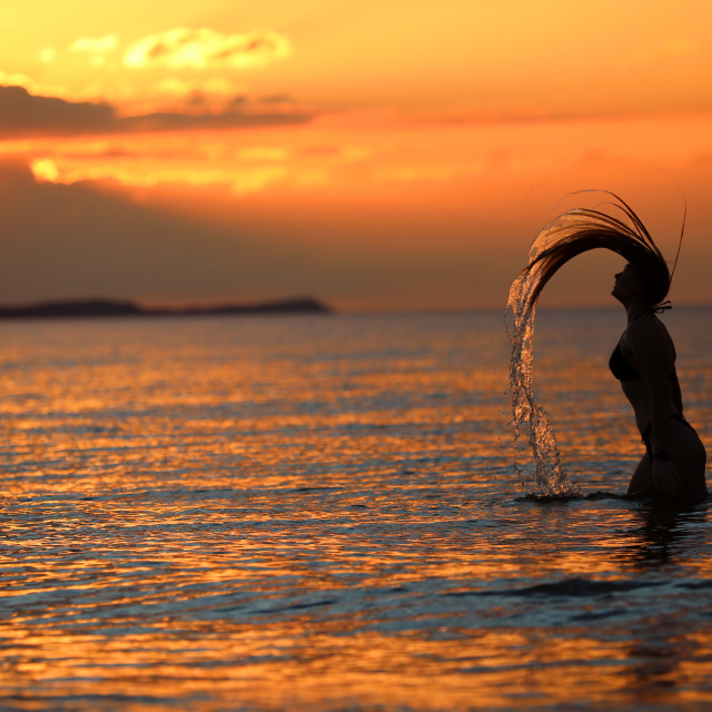 """A young girl poses for photos during the sunset"" stock image"