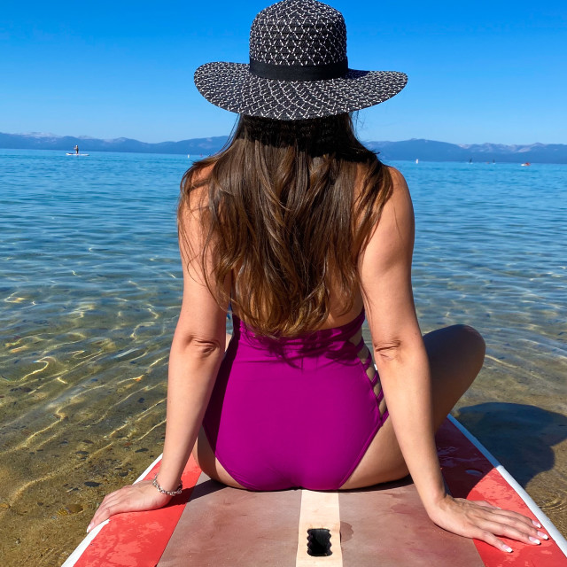 """""""Unidentifiable woman floating on paddle board"""" stock image"""