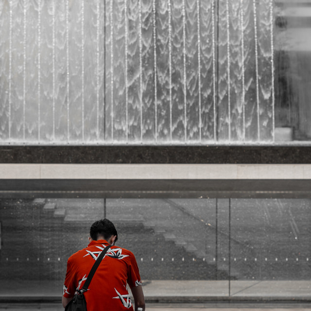 """""""A man in a red shirt sits in front of a fountain"""" stock image"""
