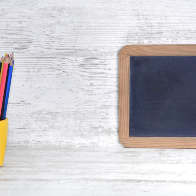 """slate on a white desk with colorful pencils in yellow pot with empty space to message"" stock image"