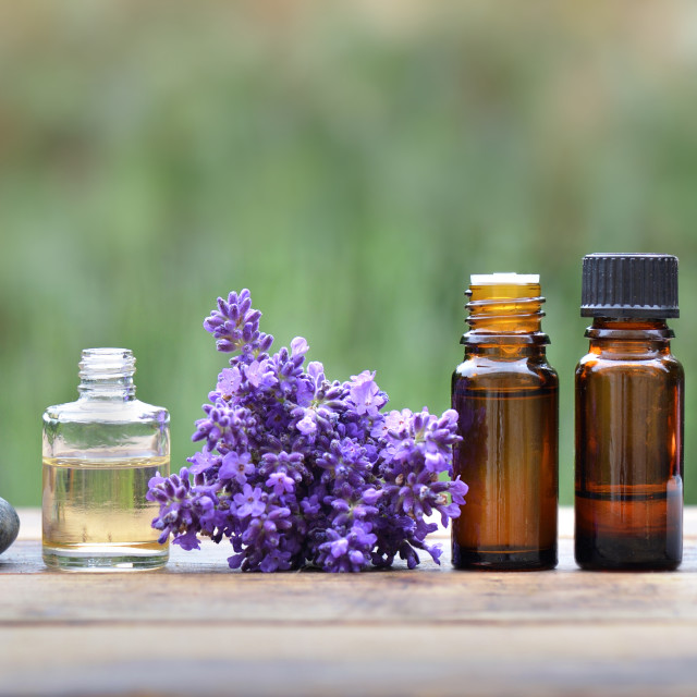 """bottles of essential oil with lavender flower arranged on a wooden table in garden with candle"" stock image"