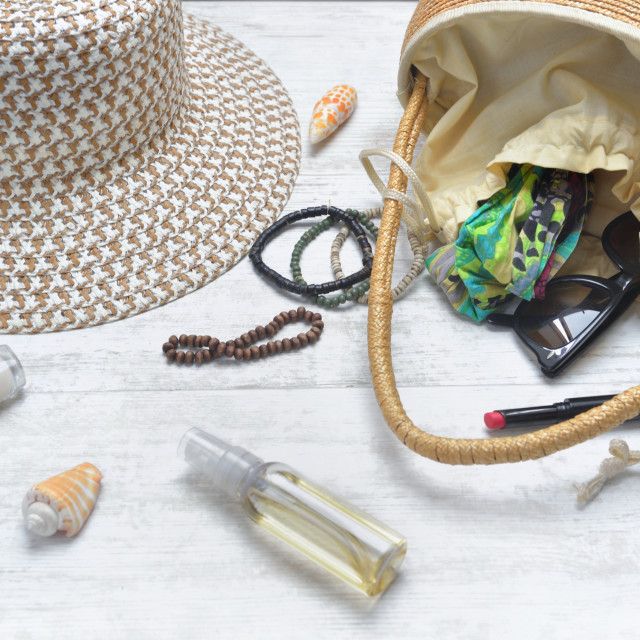 """hand bag and hat with female accessories spilled on white table"" stock image"