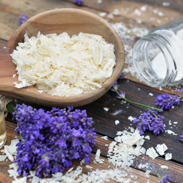 """spoon full of flakes of soap with essential oil and bunch od lavender flowers and sodium bicarbonate on wooden background"" stock image"