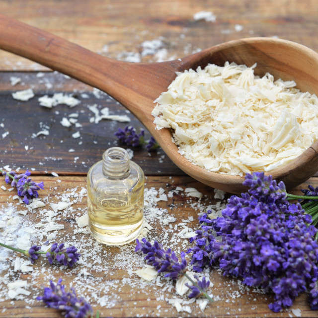 """spoon full of flakes of soap with essential oil and bunch of lavender flowers on wooden background"" stock image"