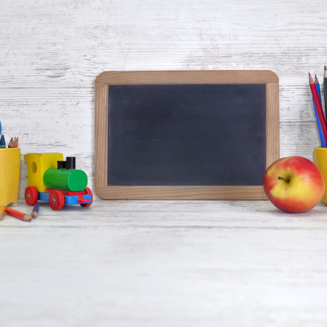 """slate on a kid desk with colorful pencils in yellow pot and an apple"" stock image"