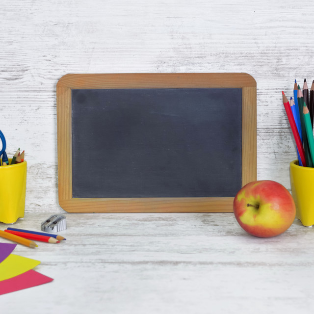 """black board on a kid desk with colorful pencils in yellow pot and an apple"" stock image"