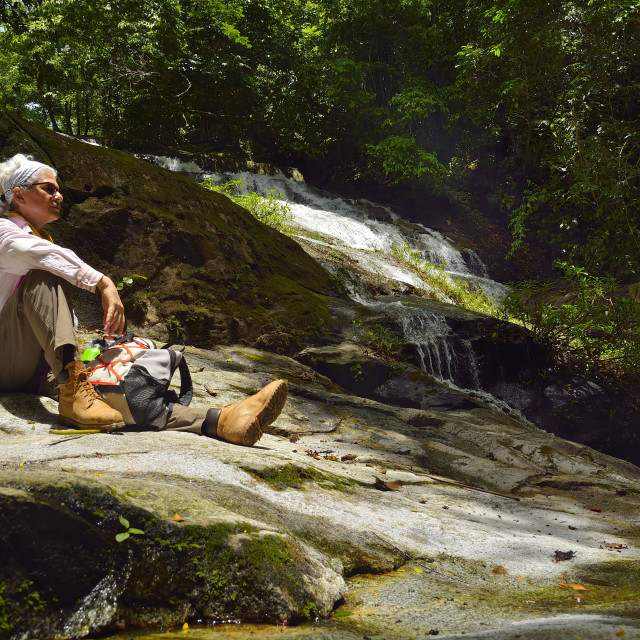 """""""Woman rests by a waterfall"""" stock image"""