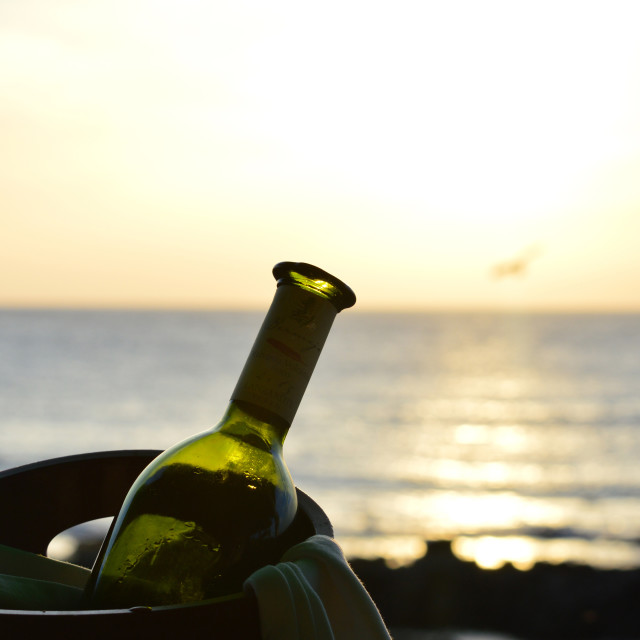 """""""Atlantic Ocean Sunset with a bottle of white wine"""" stock image"""