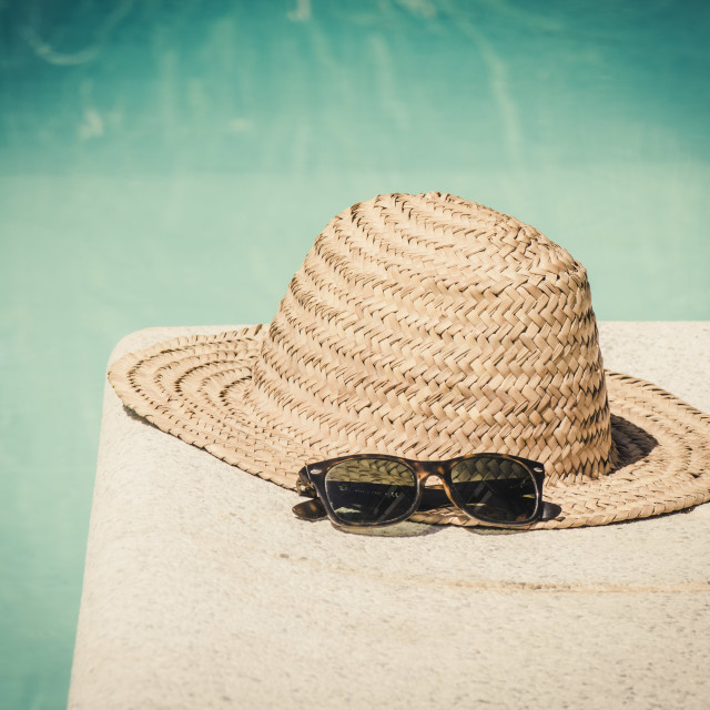 """""""Vintage straw hat with sun glasses at the border of a swimming pool in summer."""" stock image"""