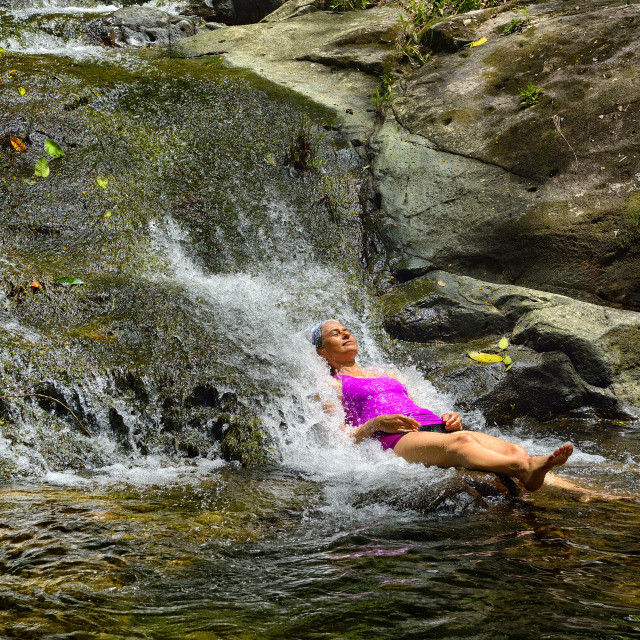 """""""Getting refreshed under a tiny waterfall"""" stock image"""