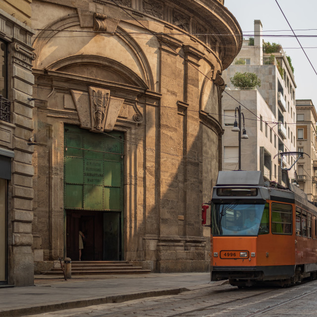 """""""A tram travels in one of the streets of an Italian city in front"""" stock image"""