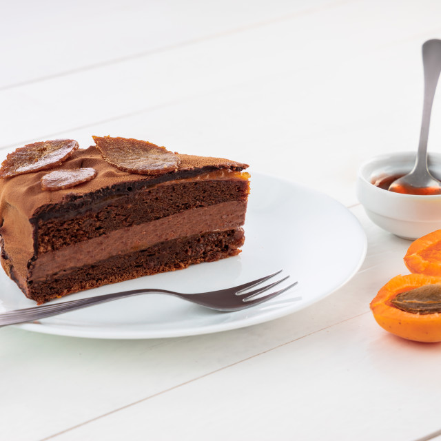 """Piece of chocolate homemade cake with nuts and apricot jelly in"" stock image"