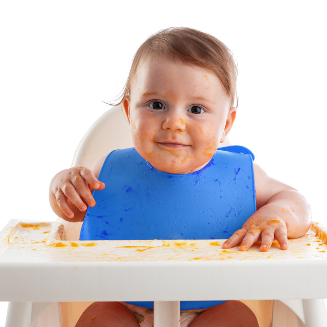 """Cheerful baby child eats food itself with hands. Portrait of hap"" stock image"