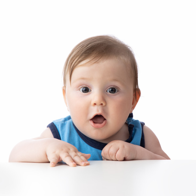 """Cute baby boy looking surprised. Child's eyes widened and mouth"" stock image"