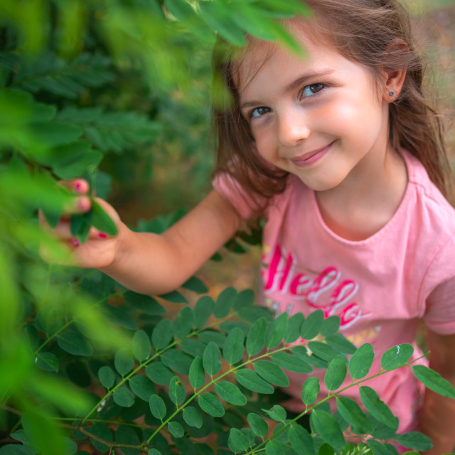 """Spring park and happy little girl playing with green tree leaves"" stock image"