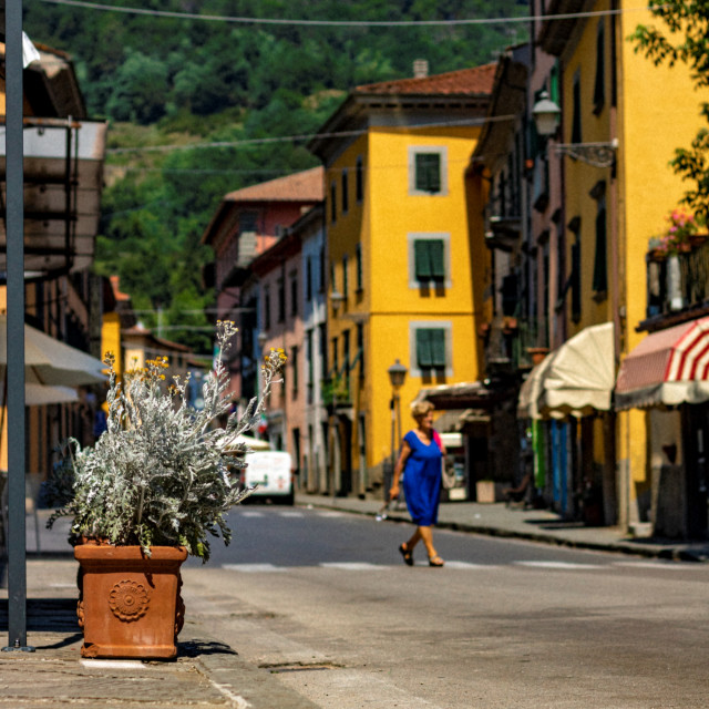"""Lady In A Blue Dress Crosses The Streets of Bagni Di Lucca - Tuscany, Italy"" stock image"