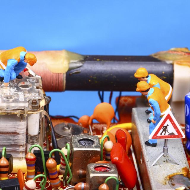 """Miniature figure workmen inspecting a vintage radio circuit board radio repair concept"" stock image"