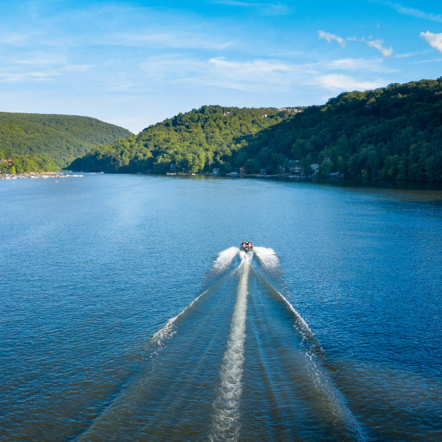 """""""Speedboat on Cheat Lake on a summer evening with boats docked in marina"""" stock image"""