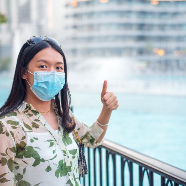 """Happy female Asian tourist wearing face mask at Dubai mall fount"" stock image"