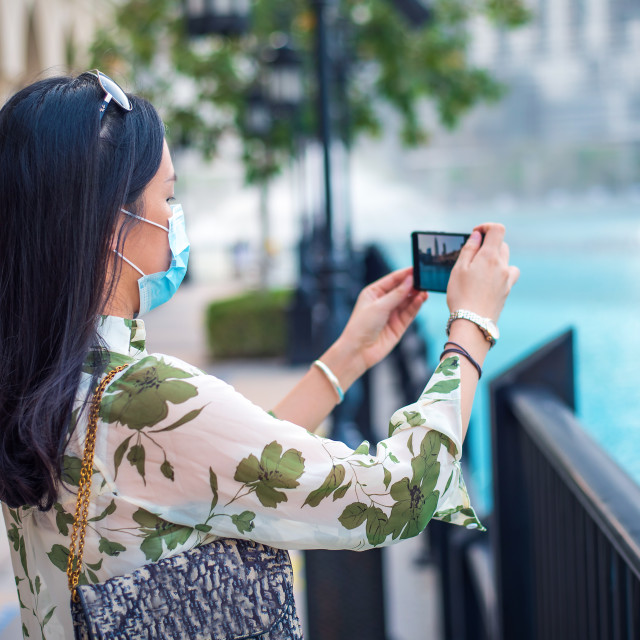 """""""Happy female Asian tourist wearing face mask and taking photo at"""" stock image"""