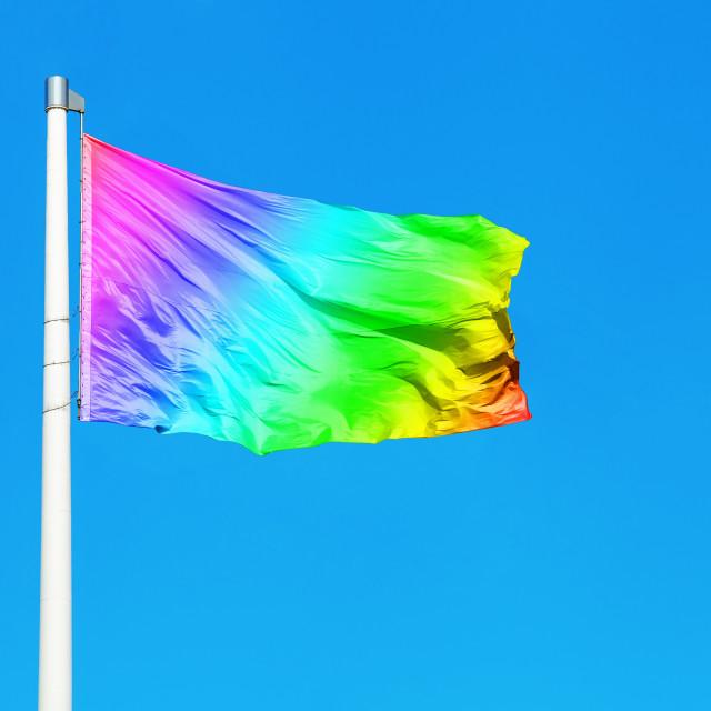 """Rainbow flag waving on the wind against clear blue sky"" stock image"