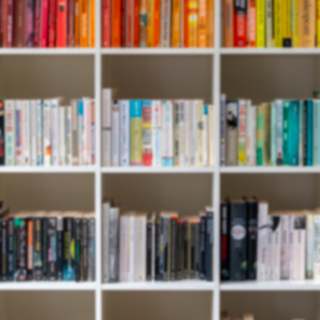 """""""Blurred image of white wooden bookcase filled with books"""" stock image"""