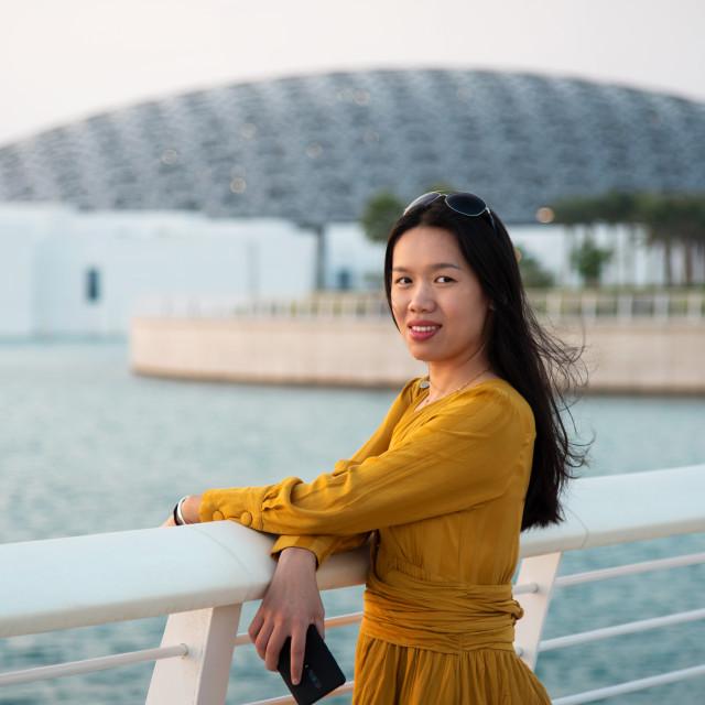 """female traveler visiting Louvre museum in Abu Dhabi emirate of the United Arab Emirates at sunset"" stock image"